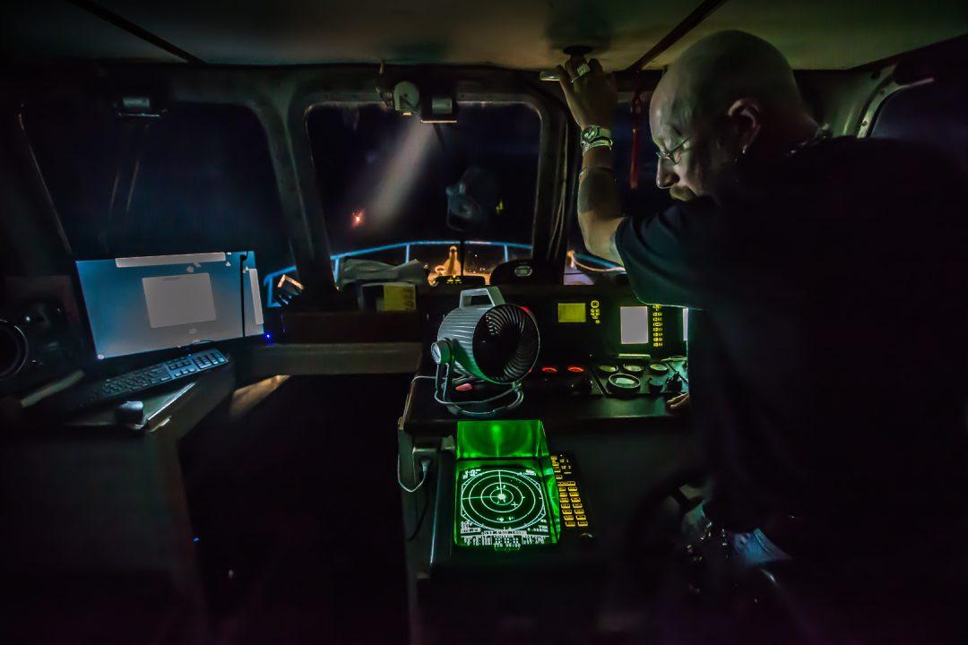 In het donker staat Ewout Adriaans achter het stuur van de Stern, een van de schepen van het N.I.O.Z.