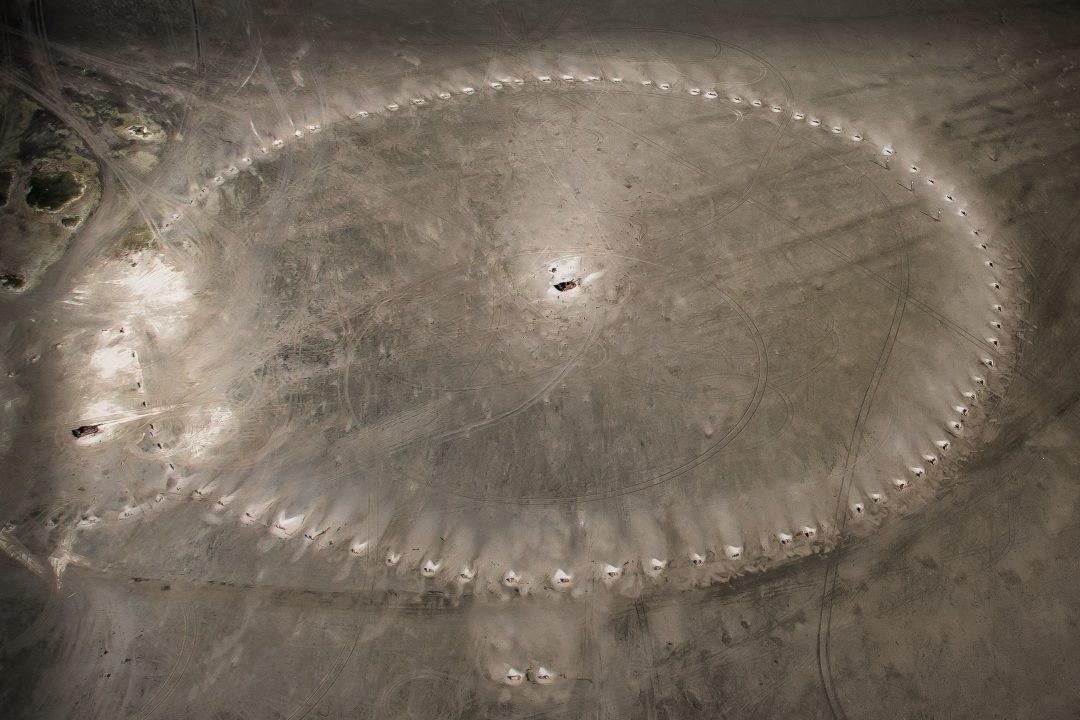 Een cirkel van helmplanten duidelijk zichtbaar vanuit een vliegtuig, door het witte stuifzand. In het midden van de cirkel stank en tank