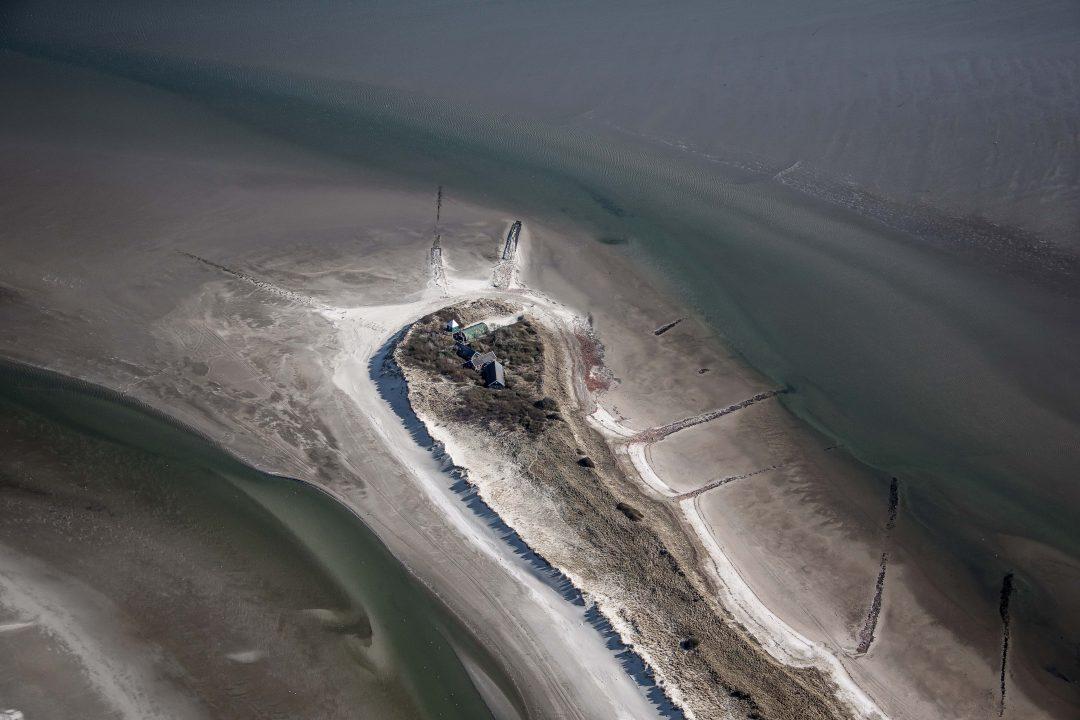 Aan het eind van de lange smalle duinenrij staat een uitkijktoren, een romneyloods en nog wat andere onderkomens